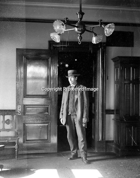 COURTHOUSE LAWMAN. Although not in uniform, this lawman is identified by a badge pinned to his vest. The bunch of keys in his hand suggest he may have been the turnkey in charge of the holding cells associated with the courtroom. The light fixture over his head provides both electricity and gas illumination. Lincoln began electric service in the late 1880s, but many homes and offices had combination fixtures for greater reliability.<br /> <br /> Photographs taken on black and white glass negatives by African American photographer(s) John Johnson and Earl McWilliams from 1910 to 1925 in Lincoln, Nebraska. Douglas Keister has 280 5x7 glass negatives taken by these photographers. Larger scans available on request.