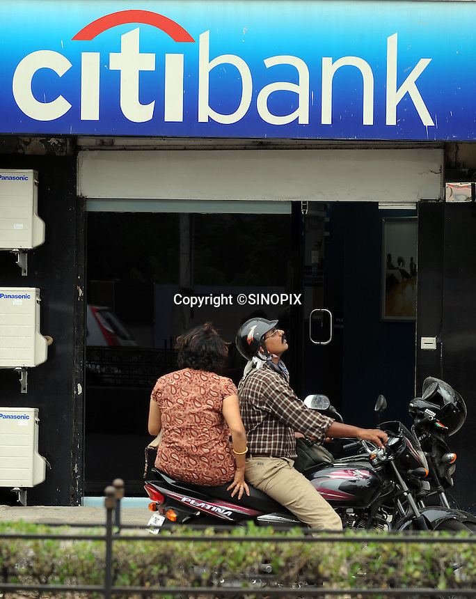 A couple sitting on the motorcycle in front of citibank in Madras, Iindia