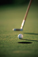 Detail image of a golf ball approaching a hole with a putter in the background.