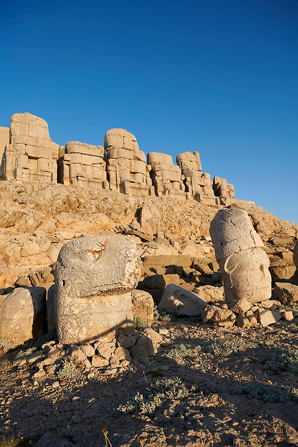 Statue heads, from left, Eagle & Antiochus with headless seated statues in front of the stone pyramid 62 BC Royal Tomb of King Antiochus I Theos of Commagene, east Terrace, Mount Nemrut or Nemrud Dagi summit, near Adıyaman, Turkey