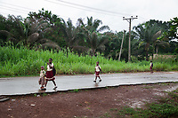 Nigeria. Enugu State. Agbani. A groupe of Igbo schoolchildren from elementary classes walk back home. The pupils, all boys and girls, wear school uniforms. The asphalt road is still wet from the last falling rain. Electric pole. 3.07.19 © 2019 Didier Ruef