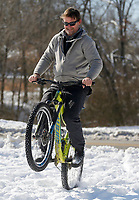 Ammen (cq) Jordan rides a wheelie Friday, February 19, 2021, after accessing the Razorback Greenway Trail on W. Cato Springs Road near the Cato Springs Branch in Fayetteville. The National Weather Service forecast for today sunny with a high near 43 degrees. Check out nwaonline.com/2102120Daily/ and nwadg.com/photos for a photo gallery.<br /> (NWA Democrat-Gazette/David Gottschalk)