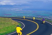 An organized bike group cruises down Haleakala's Crater Road through Haleakala Ranch with views of the central valley, pineapple and sugarcane fields and Maui's North Shore.