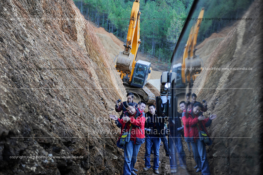 CHINA, Yunnan, Lugu Lake , bus mishap on muddy road under construction, chinese traveller give the driver directions