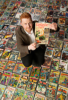BNPS.co.uk (01202 558833)<br /> Pic: ZacharyCulpin/BNPS<br /> <br /> Auctioneer, Andy Wooller with the collection, he's pictured with the rarest and most expensive comic of <br /> collection a Fantastic Four number one that is valued at £2,500<br /> <br /> A huge comic collection immaculately accumulated over 60 years by a late fanatic has been found by his family. <br /> <br /> The vast archive of over 8,000 comics was amassed by bachelor Peter James who kept them in pristine condition at his home.<br /> <br /> He was introduced to comics by his mother as a young boy as she thought it would encourage him to read.<br /> <br /> He started collecting at the age of 10 and kept the magazines neatly stacked in boxes.