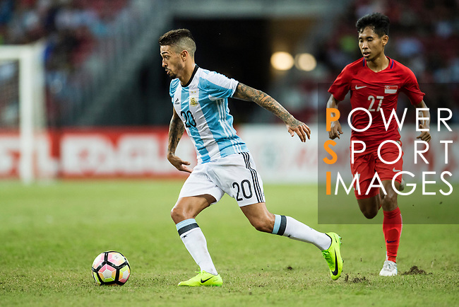 Manuel Lanzini of Argentina (L) dribbles Nazrul Nazari of Singapore (R) during the International Test match between Argentina and Singapore at National Stadium on June 13, 2017 in Singapore. Photo by Marcio Rodrigo Machado / Power Sport Images