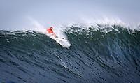 Half Moon Bay, California - January 24, 2014: 2014 Maverick's Invitational Shane Dorian to pulling out the back.