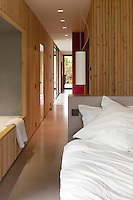 The contemporary bedroom with its built-in bath connects via a sliding door to the living area