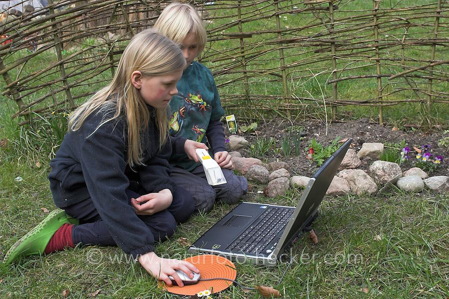 Junge und Mädchen, Kinder bestimmen Tiere und Pflanzen am Laptop im Garten mit einem digitalen Bestimmungsschlüssel, Bestimmungsübungen, hier: haben Hummel im Snappy gefangen und bestimmen die Art