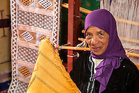 Morocco.  Amazigh Berber Woman Displaying Rug, Ait Benhaddou Ksar, a World Heritage Site.
