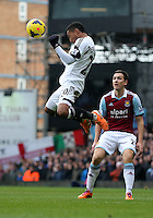 Pictured L-R: Jonathan de Guzman of Swansea heads the ball away, against Stewart Downing of West Ham looks on. 01 February 2014<br /> Re: Barclay's Premier League, West Ham United v Swansea City FC at Boleyn Ground, London.
