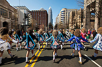Members of the Rince na h'Eireann Irish Dancers kick up their heels  as they make their way down Tryon Street during the annual St. Patrick's Day Parade in uptown Charlotte, North Carolina.