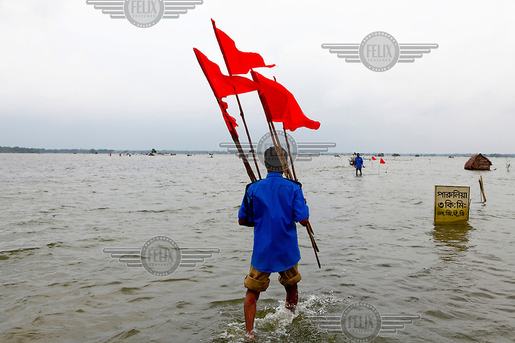 A man uses red flags to mark the path of a road submerged  beneath flood waters that have innundated the Satkhira district. Each year limited flooding helps to enrich the soil and create very fertile farm land. In turn, this results in a high population density on the flood plain. However, the low lying land is also prone to extreme flooding events that are very destructive and to both economy and life..
