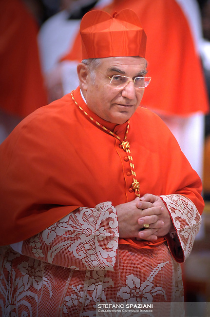 Italian newly appointed Cardinal Paolo Romeo (C) gets his biretta, the square red hat symbolising the blood of the martyrs, from Pope Benedict XVI (L) on November 20, 2010 during a consistory at St Peter's basilica at The Vatican. 24 Roman Catholic prelates join today the Vatican's College of Cardinals, the elite body that advises the pontiff and elects his successor upon his death