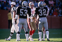 SAN FRANCISCO, CA - Joe Montana of the San Francisco 49ers meets Rod Martin and Marcus Allen of the Oakland Raiders at midfield before a game at Candlestick Park in San Francisco, California in 1987.  Photo by Brad Mangin