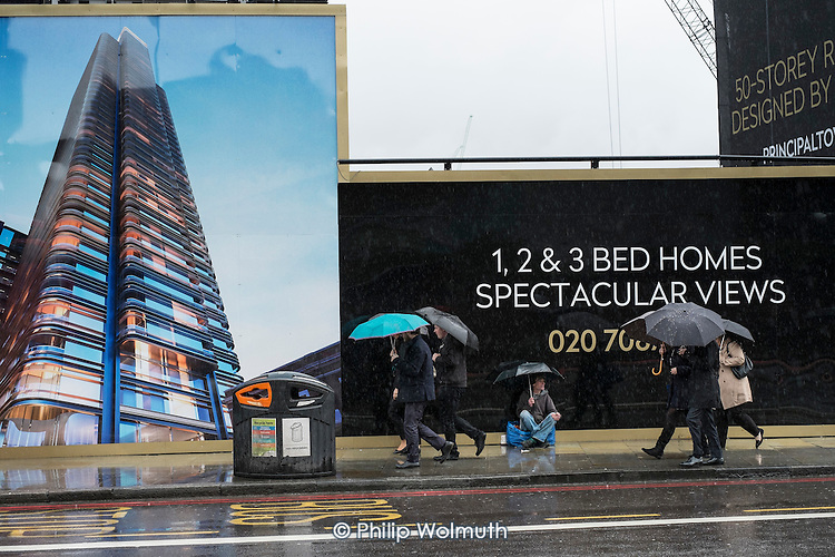 Rough sleeper begging outside a luxury housing development, Shoreditch, London.