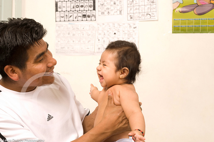 Father holding 4 month old baby girl, enjoying her laugh