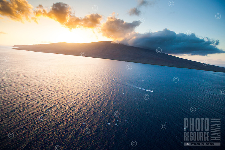 As the sun sets, a boat sails towards Maui from Lana'i.