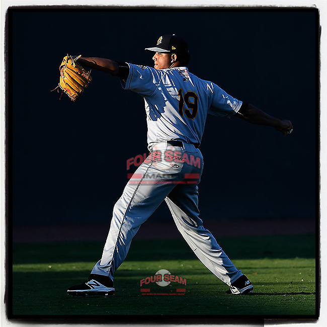 Starting pitcher Rony Garcia (19) of the Charleston RiverDogs warms up into the setting sun before Game 2 of the South Atlantic League Southern Division Playoff against the Greenville Drive on Friday, September 8, 2017, at Fluor Field at the West End in Greenville, South Carolina. Charleston won, 2-1, and the series is tied at one game each. (Tom Priddy/Four Seam Images)