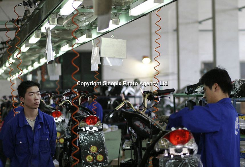 Workers install components onto a LPG scooter at the Shanghai Forever Bicycle Factory in Shanghai, China. With the worsening of the city's air pollution due to increased vehicle traffic, the city has banned the sales of gasoline powered scooters in favor of ones that run on cleaner LPG..21-APR-04