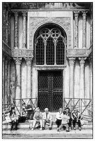 Tourists resting on the steps of a church doorway, Venice, Italy.