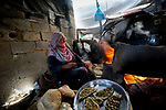 A Palestinian woman bakes bread and pies in a traditional clay oven in Khan Yunis in the southern Gaza Strip on March 5, 2020. Photo by Osama Baba