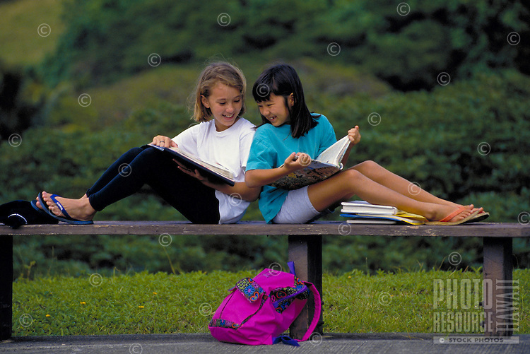 Two girls, ages 8 and 10 study together outdoors after school.