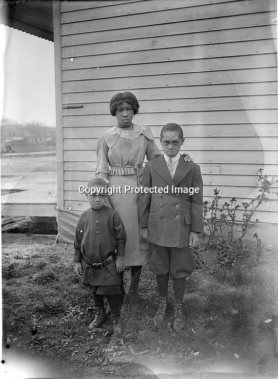 SISTER AND BROTHERS (see addendum below). The two boys, probably brothers, are dressed quite differently, reflecting their ages. The younger fellow wears a long tunic over his knickers, while the older boy has a double-breasted coat, shirt, and tie--plus knickers. The young woman wears a tailored dress, lace collar, and button shoes. There were several seamstresses in Lincoln's African American community.<br /> <br /> Information added by Stan Schmunk February 2017: <br /> I've positively identified her as Gladys Easley. The older boy is her brother James Richurd while the younger boy is her nephew Willard Arthur, the son of Gladys' older brother Clifford, who was a widower. Gladys was born in Lincoln in 1906 and passed also in Lincoln in 1948. Her grandfather, David, was a Civil War hero, who fought for the 1st Kansas Col Infantry (later the 79th USCT. This group endured a horrible slaughter but David survived and moved his family to White Cloud, Kansas in 1865. In 1871 a son, Jerome, was born. David passed sometime between 1875 and 1880. By the late 1890s Jerome was in Omaha and in 1901 he moved to Lincoln. He was a sometime policeman and common laborer. Gladys never went to high school and worked her entire life as a domestic, seamstress, cook, etc. including working for a NU fraternity. <br /> <br /> Photographs taken on black and white glass negatives by African American photographer(s) John Johnson and Earl McWilliams from 1910 to 1925 in Lincoln, Nebraska. Douglas Keister has 280 5x7 glass negatives taken by these photographers. Larger scans available on request.