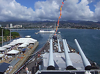 Sweeping view of Pearl Harbor showing the Arizona memorial, Ford Island bridge, battleship Missouri bow and guns, and Pearl City beyond.