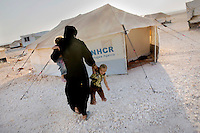 A woman carries her two children to her UNHCR tent in Zaatari Refugee Camp. Approximately two million people have fled the conflict in Syria. At least 130,000 of them live in Zaatari Refugee Camp, although it was designed to house 60,000, and a further 2,000 people arrive each day.