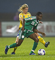 Sweden forward (11) Victoria Svensson is held off by Nigeria midfielder (15) Maureen MMadu. Sweden (SWE) tied Nigeria (NGA) 1-1 during a FIFA Women's World Cup China 2007 opening round Group B match at Chengdu Sports Center Stadium, Chengdu, China, on September 11, 2007.