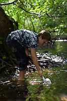 Junge mit Kescher an einem Bach, Keschern