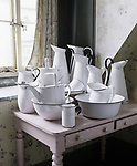 A group of enamel jugs and basins on a pink table by a window at Tyntesfield. These were the servants' sanitary ware for washing.