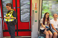 Switzerland. Canton Ticino. A police officer from TPO (Transport Police) on a TILO train between Bellinzona and Lugano. The policewoman is checking on her mobile phone train schedules. Two students ride the morning train on their way to schools. TPO (Transport Police) is the Swiss Federal Railways Police. Swiss Federal Railways (German: Schweizerische Bundesbahnen (SBB), French: Chemins de fer fédéraux suisses (CFF), Italian: Ferrovie federali svizzere (FFS)) is the national railway company of Switzerland. It is usually referred to by the initials of its German, French and Italian names, as SBB CFF FFS. TILO (Treni Regionali Ticino Lombardia) creates efficient train connections between the towns in the canton Ticino.12.06.2017 © 2017 Didier Ruef