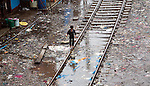 Mumbai, India<br /> Bandra area slums - Boy walking on the rails in torrential rain on  rubbish strewn slum area next to the station<br /> Picture by Gavin Rodgers/ Pixel8000<br />  07917221968