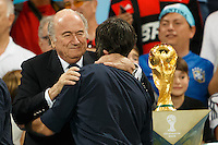 Germany manager Joachim Low hugs FIFA president Sepp Blatter and walks past the World Cup trophy