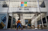 NEW YORK, NEW YORK - MARCH 10: A woman walks in front a Microsoft store on March 10, 2021, in New York. The Nasdaq Composite continued falling more than half a percent during the day also the move away from Apple Inc, Amazon.com Inc , Facebook Inc, Tesla Inc and Microsoft Corp, falling during the day, helped small-cap stocks rise more than double the gains of the S&P 500. (Photo by John Smith/VIEWpress)