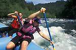 Two young women paddling inflatable raft through whitewater on the North Umpqua River; Cascade Mountains, Oregon.