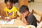 Education preschool 4-5 year olds sad angry frustrated boy covering face with hands sitting next to girl doing art project at table horizontal