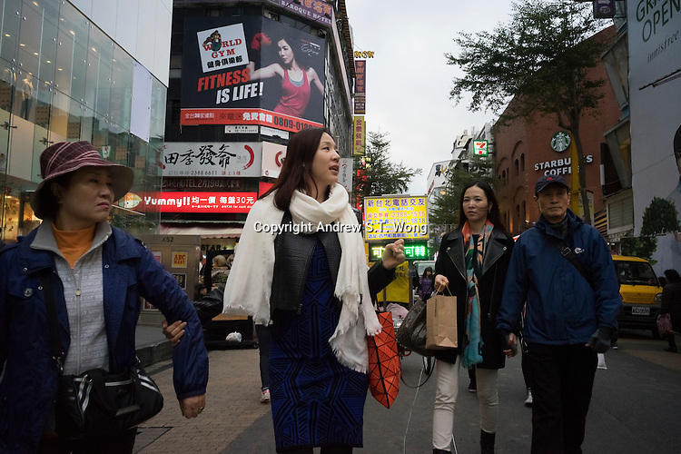 """Tourists visit Ximending District in Taipei, Taiwan, 2015. Ximending has been a famous area for shopping and entertainment since the 1930s. Historic structures include a concert hall, a historic cinema, and the Red House Theatre. Modern structures house karaoke businesses, art film cinemas, wide-release movie cinemas, electronic stores, and a wide variety of restaurants and fashion clothing stores. The pedestrian area is especially popular with teens and has been called the """"Harajuku"""" of Taipei."""