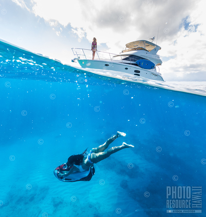 A woman rides an underwater sled as her friend watches during a fun day on a power cruiser off of Waikiki, O'ahu.
