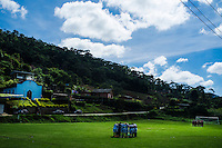 Soccer game in countryside Brazil. Players pray together before game, catholic church in background. Nova Friburgo city rural area, Rio de Janeiro state.