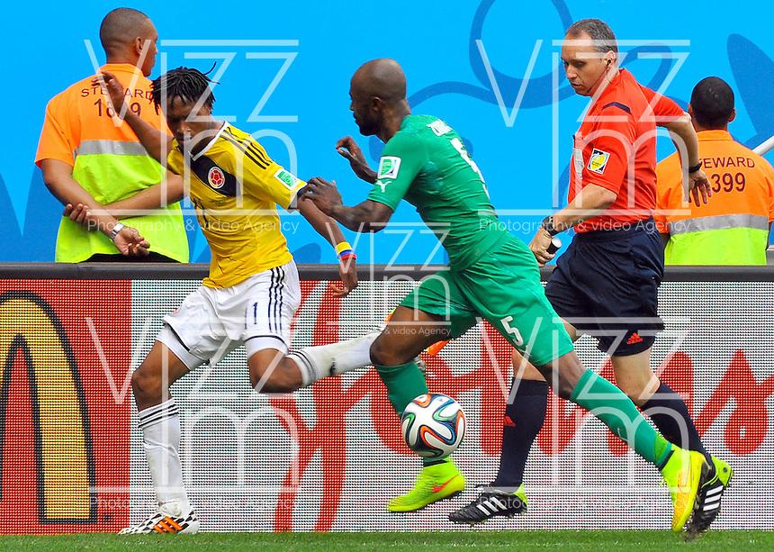 BRASILIA - BRASIL -19-06-2014. Juan Cuadrado (#11) jugador de Colombia (COL) disputa el balón con Didier Zokora (#5) jugador de  Costa de Marfil (CIV) durante partido del Grupo C de la Copa Mundial de la FIFA Brasil 2014 jugado en el estadio Mané Garricha de Brasilia./ James Rodriguez (#11) player of Colombia (COL) fights the ball with Didier Zokora (#5) player of Ivory Coast (CIV) during the macth of the Group C of the 2014 FIFA World Cup Brazil played at Mane Garricha stadium in Brasilia. Photo: VizzorImage / Alfredo Gutiérrez / Contribuidor