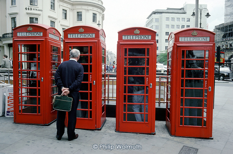 Man waiting outside traditional red English telephone kiosks in The Strand, London.
