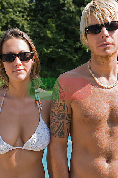 young cool good looking couple in swimwear by pool look neutral or serious to camera