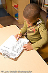Education Preschool 4-5 year olds start of day boy signing in on name sheet vertical