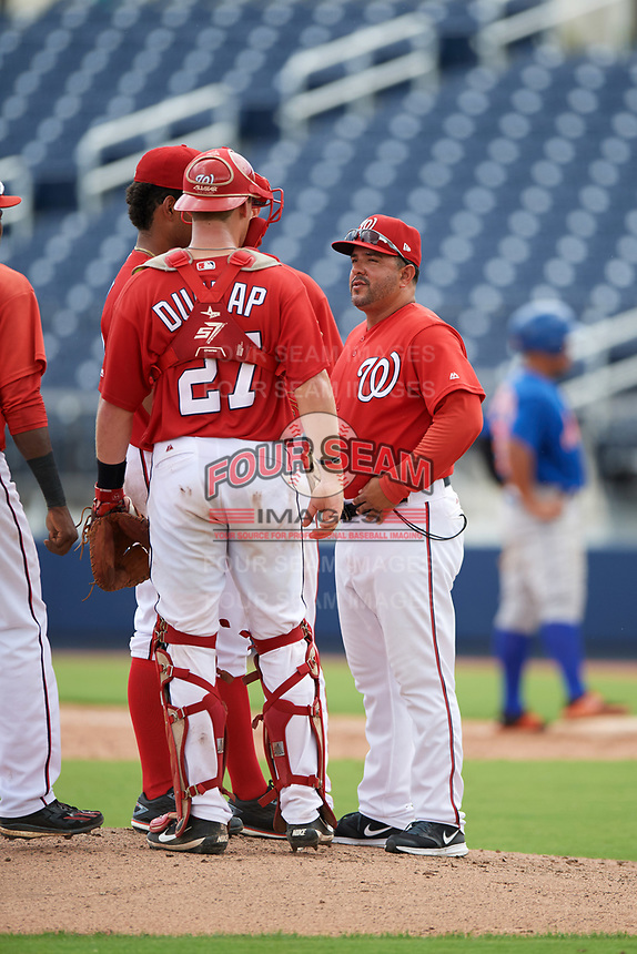 GCL Nationals pitching coach Michael Tejera (58) talks with starting pitcher Malvin Pena (37) and catcher Alex Dunlap (27) during the second game of a doubleheader against the GCL Mets on July 22, 2017 at The Ballpark of the Palm Beaches in Palm Beach, Florida.  GCL Mets defeated the GCL Nationals 4-1.  (Mike Janes/Four Seam Images)