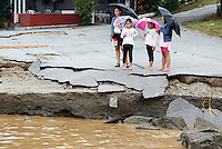 Onlookers by a road that has collapsed in Nea Mihaniona