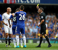 Oscar of Chelsea is shown a yellow card from Referee Michael Oliver   during the Barclays Premier League match between  Chelsea and Swansea  played at Stamford Bridge, London