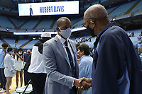 CHAPEL HILL, NC - APRIL 6: UNC men's basketball head coach Hubert Davis shakes hands with former UNC and professional basketball player Bill Chamberlain after after his introductory press conference at Dean E. Smith Center on April 6, 2021 in Chapel Hill, North Carolina.